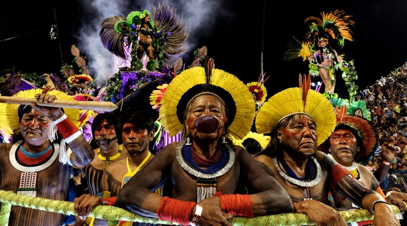 The leader of the Kayapo indigenous people Raoni Metuktire (C), Megaron Txucarramae (2-R) and other indigenous leaders parade with the Imperatriz Leopoldinense samba school during the first night of Rio's Carnival at the Sambadrome in Rio de Janeiro, Brazil, early on February 27, 2017. / AFP PHOTO / Yasuyoshi CHIBA
